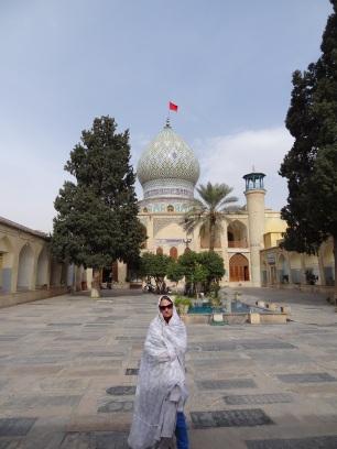 Anne mit Tschador vor einem islamischen Schrein